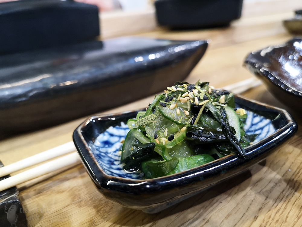 In a rectangular small bowl, black on the outside and white with blue eyes inside, lies a serving of green cucumber and wakame algae salad. Topped with black and light sesame seeds.