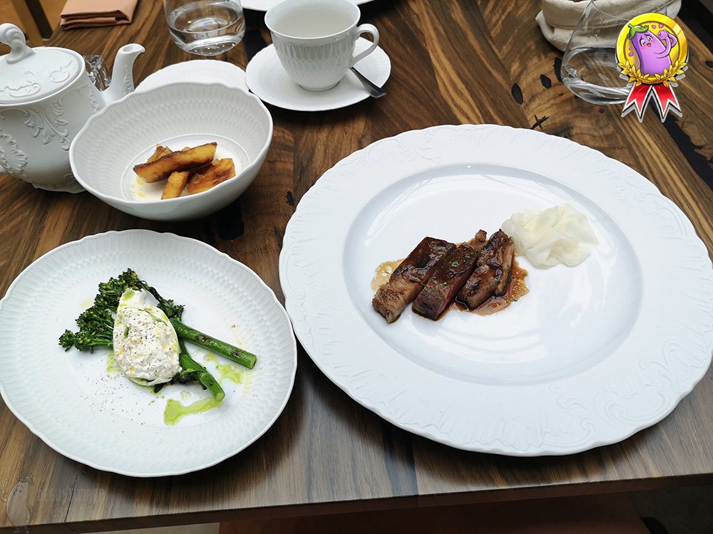 On the table is a large plate with sliced beef and kohlrabi flakes. Next to it is a platter with grilled wild broccoli and burrata and a white bowl with pieces of oven potatoes partially dipped in buttermilk.