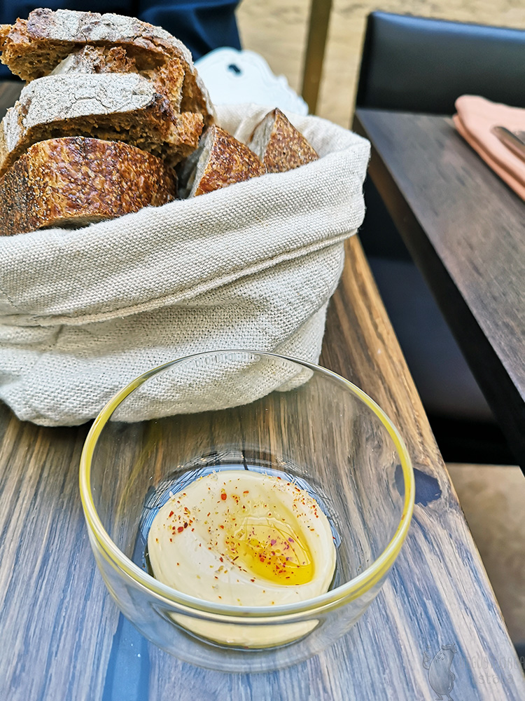 A small glass bowl of butter sprinkled with paprika and topped with oil, a basket bag of bread.