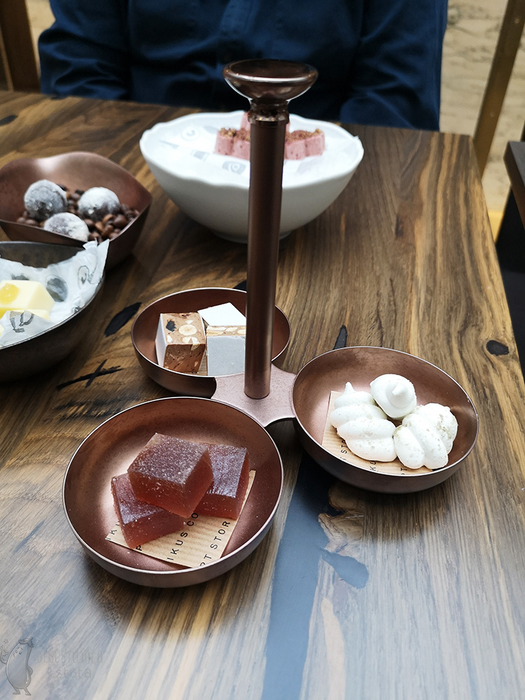 Copper three bowls joined together. In them separately: nougat with nuts, meringue and jelly beans in sugar.