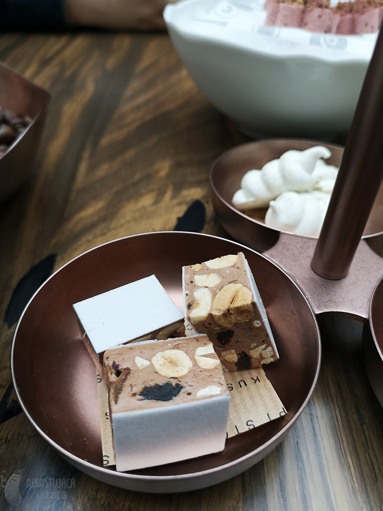 There are three pieces of nougat in a copper bowl.