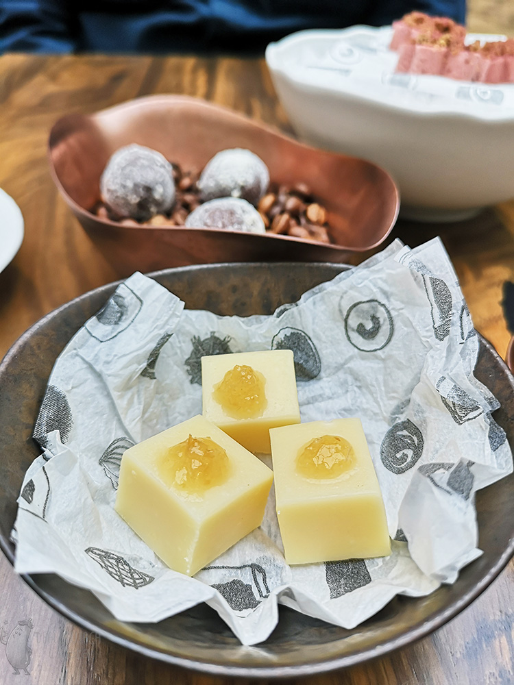 In a metal bowl are three cubes of white chocolate with yellow jam on top.