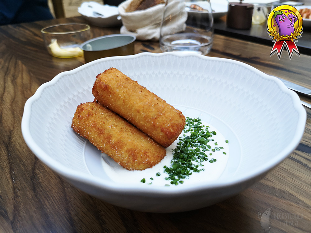 Arranged in a white bowl with cream are 3 thick, breaded polenta fries.