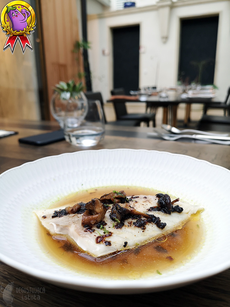 A piece of perch without skin is in a broth in a deep, white plate. Topped with pieces of shiitake mushrooms.