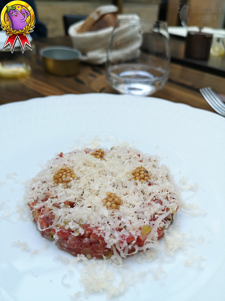 On a flat white plate lies a flat disk of tartare sprinkled with grated cheese.