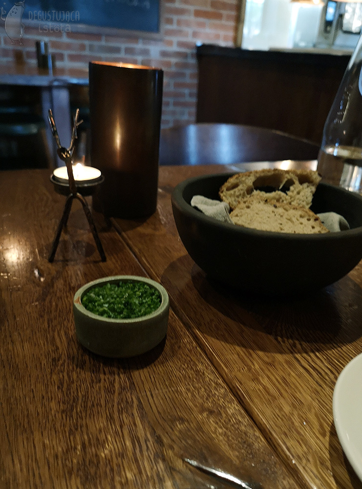 On a wooden table there is a small bowl with butter covered with chopped chives and next to it a bigger, black bowl with slices of bread.