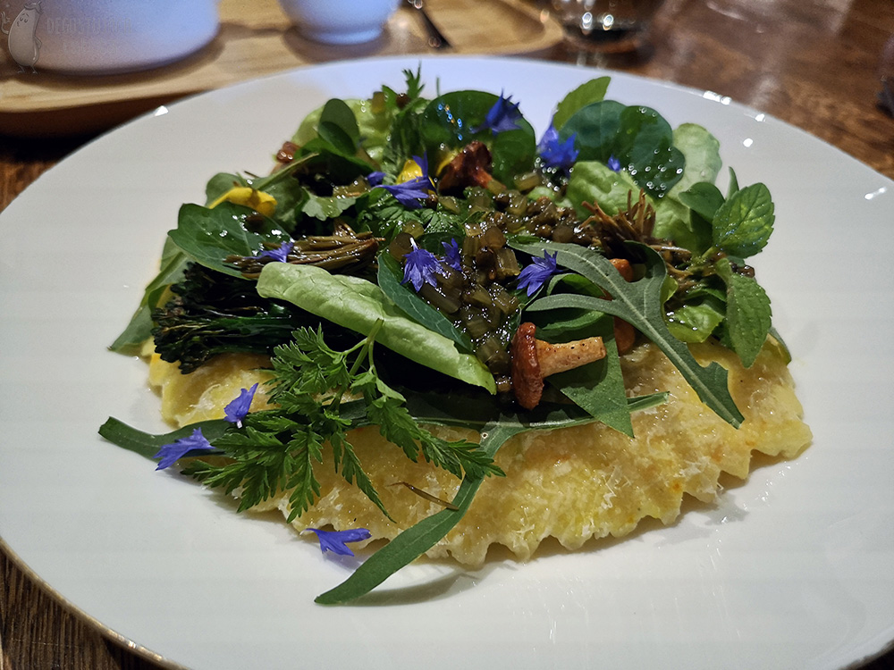 Large one ravioli covered with green shoots, Lettuce leaves and herbs and small blue flowers.