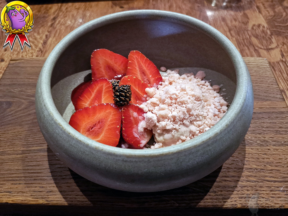 In a small brown bowl, they are cut up, large strawberries, on which two small pine cones are lying and a portion of the panna cotta lies next to it.