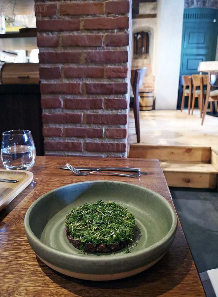 In a grey, flat bowl there is a disc tartar covered from the top with a thick layer of cress.