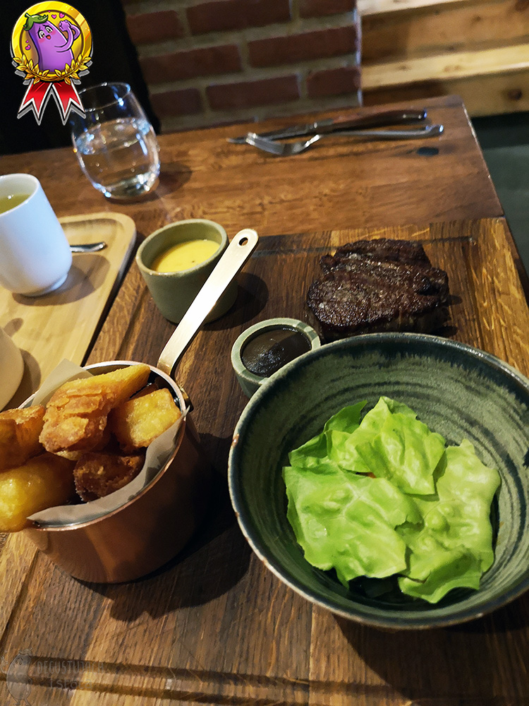 On a wooden board next to the steak there is a small bowl with a brown mushroom ketchup, bowl with lettuce, pan with fries and a cup with hollandaise sauce.