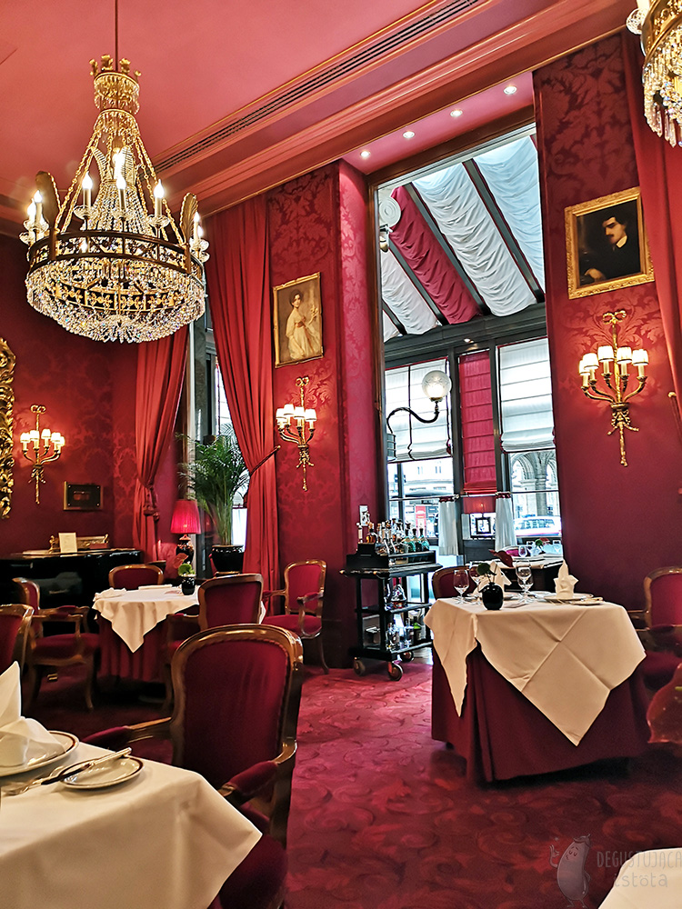 A view of the center of the restaurant room. A crystal, gold-plated chandelier hangs from the ceiling. The carpeting on the floor is also red.