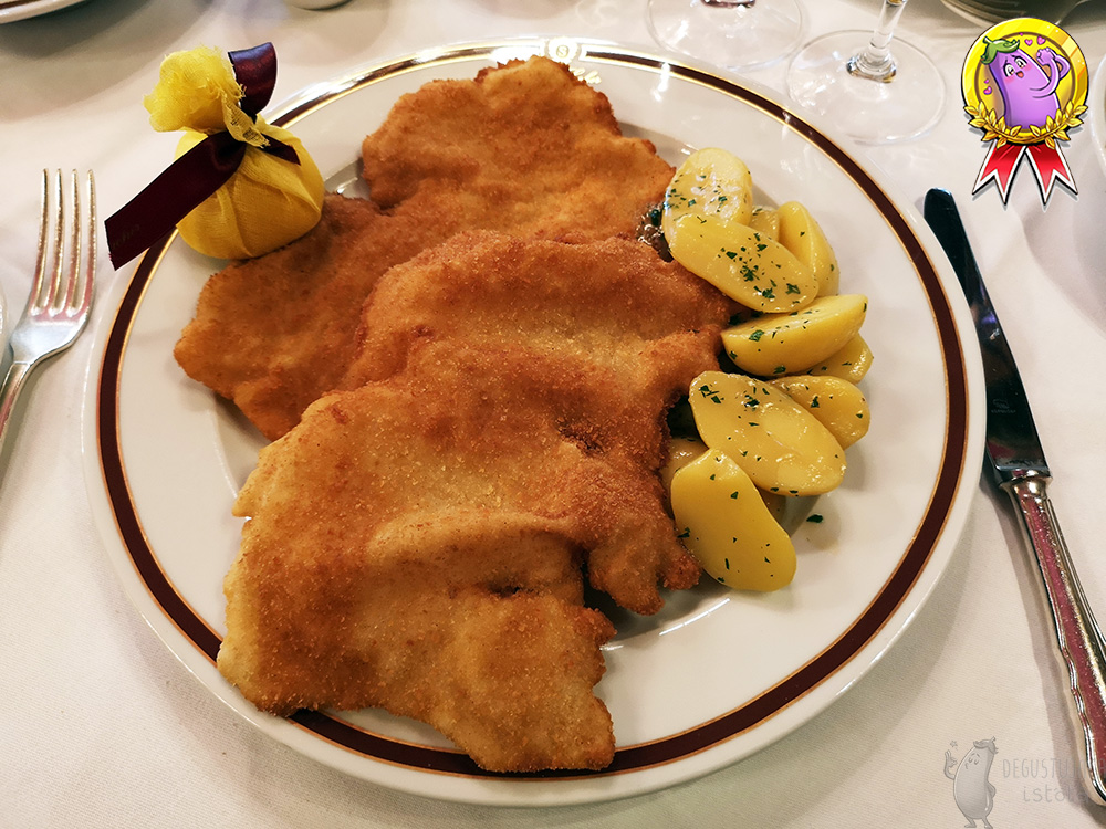 On a large flat plate lie two schnitzels, one on top of the other. To the right of the schnitzels are halves of potatoes, poured with fat and sprinkled with parsley. On the left side there is a lemon half wrapped in a yellow net, tied with a maroon ribbon.