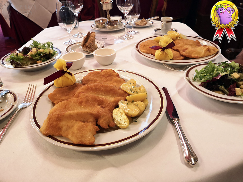 On a table with a white tablecloth are two large, flat plates with schnitzels and two deep plates with salads.