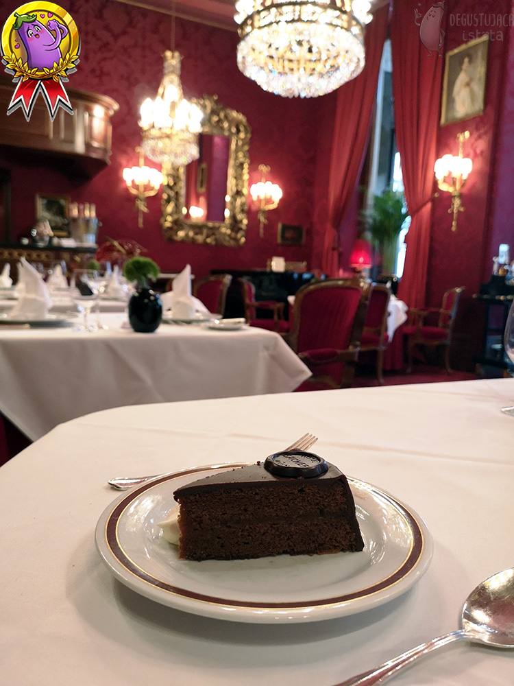 A piece of chocolate cake with a portion of whipped cream on a small white plate. Next to it there is silver cutlery. In the background there is a view of the restaurant room.
