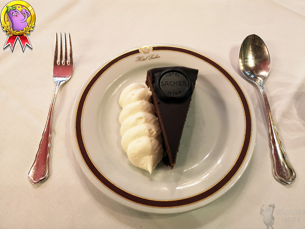 A piece of chocolate cake with a portion of whipped cream on a small white plate. Next to it there is silver cutlery. Top view of the cake.