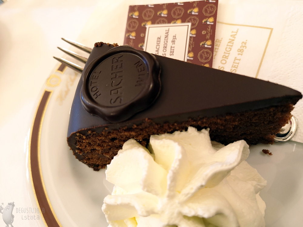 A piece of chocolate cake with a portion of whipped cream on a white small plate.