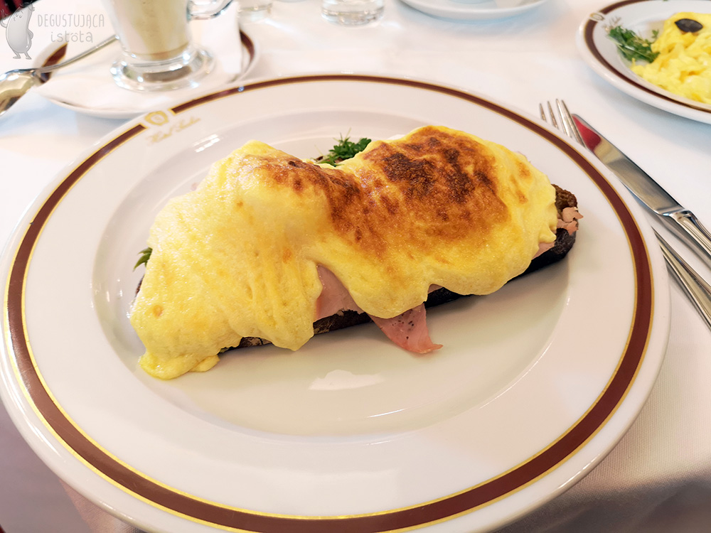 A slice of bread doused with top-baked hollandaise sauce. Ham sticks out from under the sauce. The bread lies on a white flat plate with the logo of Hotel Sacher.