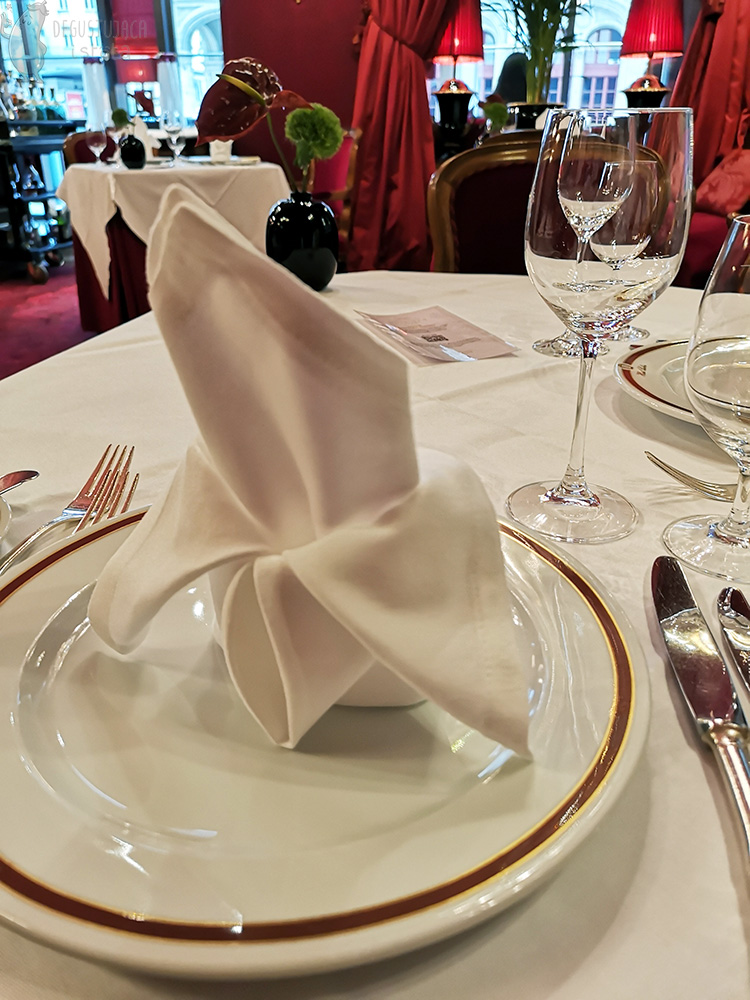 Beautifully folded white napkin placed on a plate with Hotel Sacher logo. Next to it there is silver cutlery.