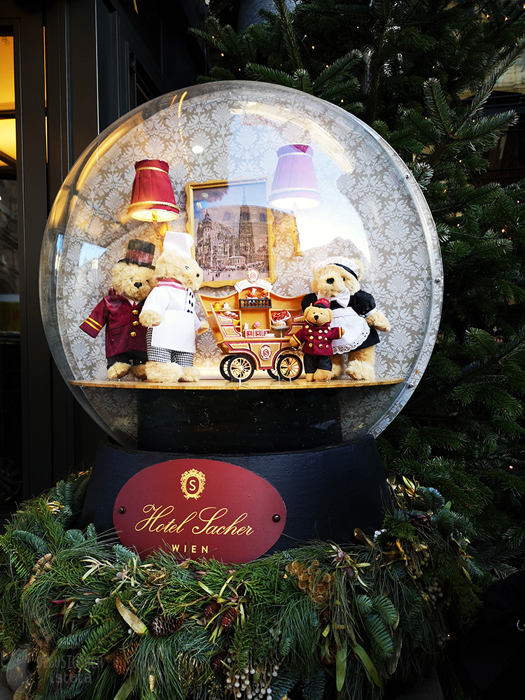 Large transparent ball with three big teddy bears and one little bear. One big bear sells sweets from his stall on wheels. The ball stands on a black stand with the Sacher Hotel logo.