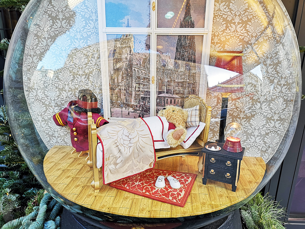 The inside of the second snow globe. One teddy bear is sleeping in a bed. Behind the bed is a small window with a view of St. Stephen's Cathedral. By the bed, on a table lies a piece of Sacher cake, a lamp and a mini snow globe.