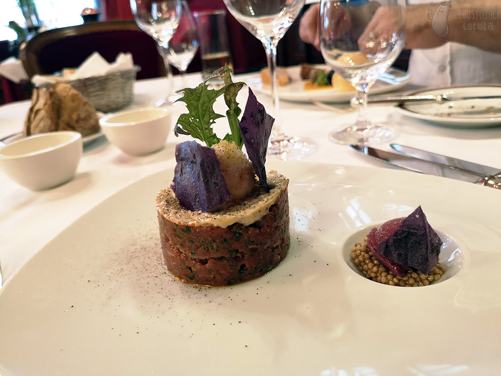 On the white plate to the left is tartare, arranged in a disc, smeared on top with mayonnaise, garnished with green and purple leaves. On the right, a portion of mustard and grape ice cream is arranged in the spherical hollow of the plate.