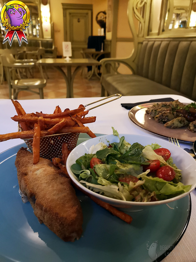 On a flat, blue plate lies a coated piece of halibut and in a melted basket of sweet potato fries. On the plate there is also a bowl with a salad with cocktail tomatoes.