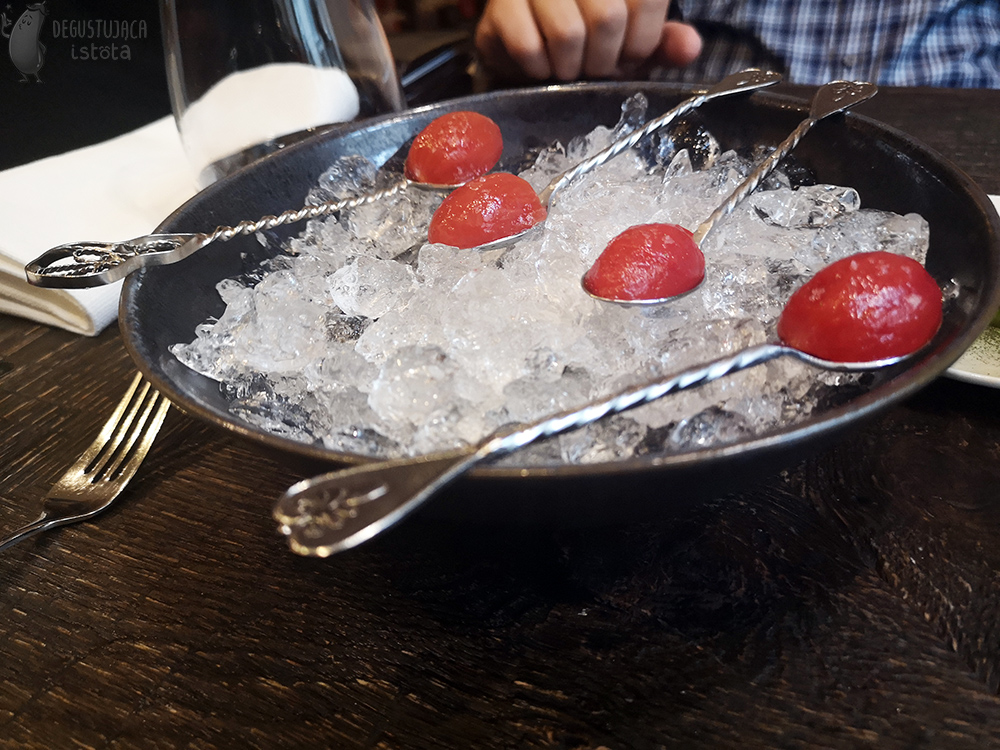 A bowl of ice with small tomatoes on it without skin on silver spoons.