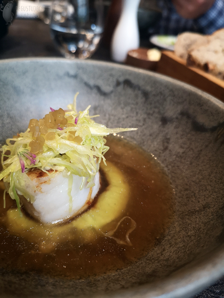 Portion of cod on green puree in a bowl. Up to half the height of the cod, the bowl is filled with broth. There are strips of cabbage on the cod.