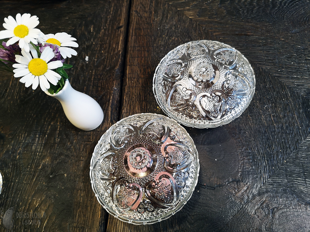 Crystal containers on a wooden table. In addition, a white vase with wild flowers.