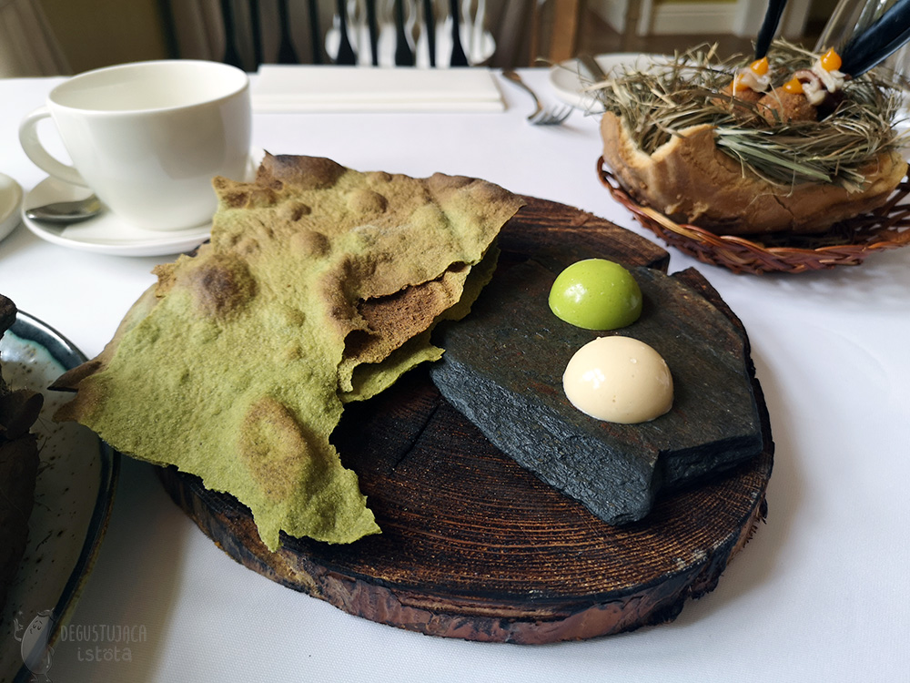 Slightly greenish scones on a piece of wood. Next to it, on the same wood, on a piece of slate, there are two domes of butter. One greenish and one beige.