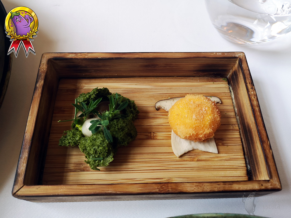 In a flat wooden box there is a fried yolk on a slice of oyster mushroom and a green lovage moss on the left.