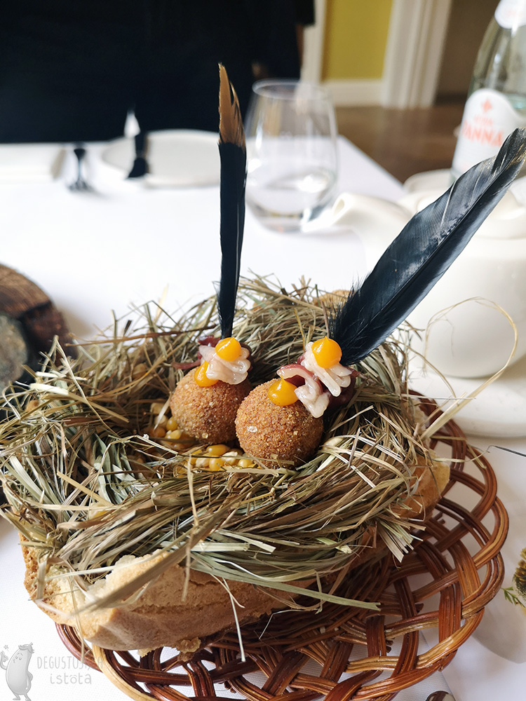 In a hay wreath placed in a bun and placed on a wicker basket, there is an amuse-bouche that is impaled on a black feather. They are padded balls and a rolled up slice of Półgęsek. Decorated with dots of orange sea buckthorn gel.