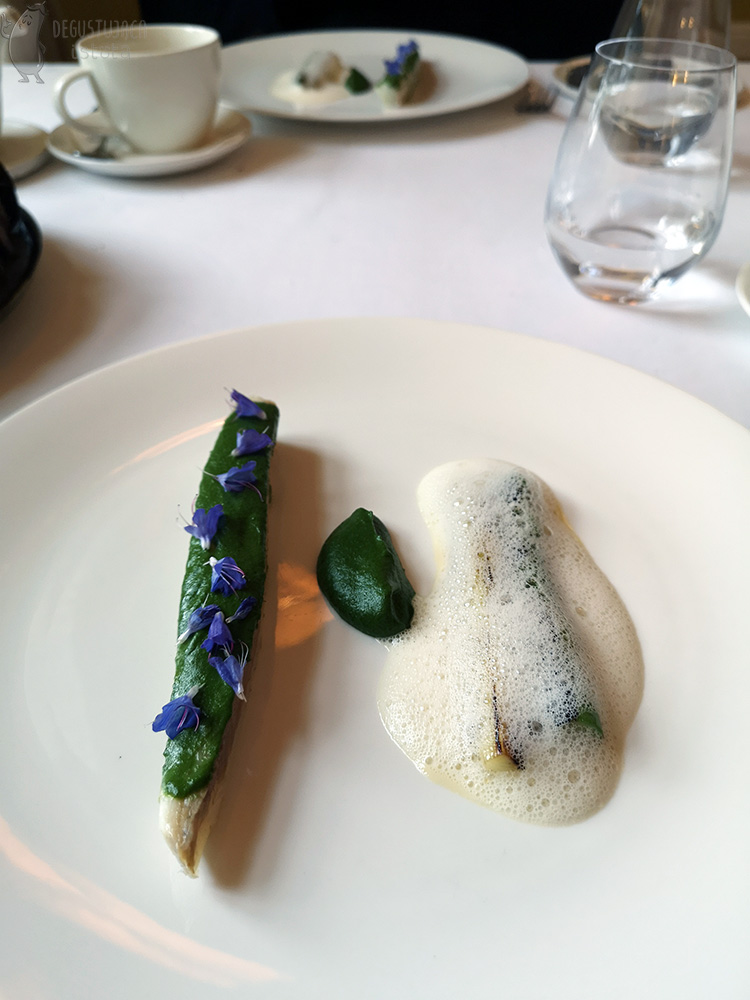 On the flat white plate to the left is a strip of perch smeared on top with spinach puree and decorated with blue flowers. A portion of the same puree is placed in the center, and on the right is white asparagus and leek covered in butter foam.