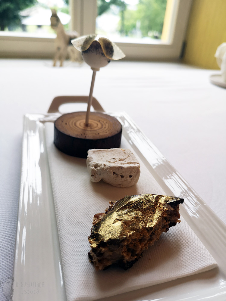 On a flat, rectangular plate lie from the front: a lump of coconut painted gold, a piece of light nougat and a white round lollipop covered with a transparent jelly like a frill on the top.