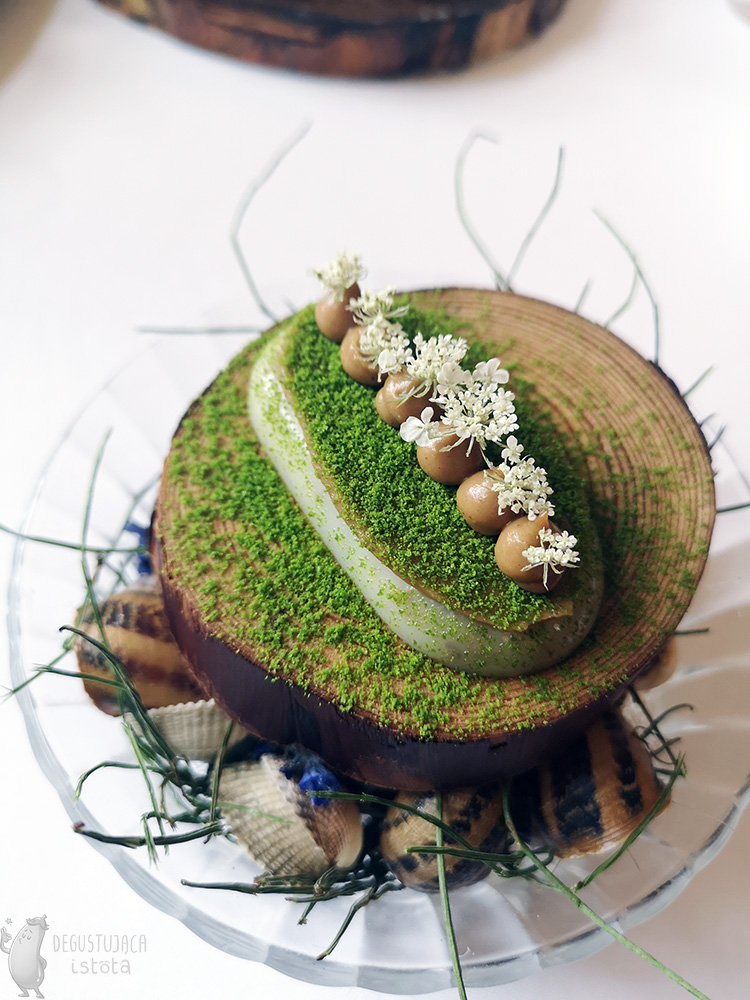 In a glass bowl filled with snail shells, there is a piece of wood with a flat layer of lard on it and a brown layer with roasted garlic puree on it. Both layers are sprinkled with green powder. At the top of the layers in a row are small portions of puree decorated with white flowers.