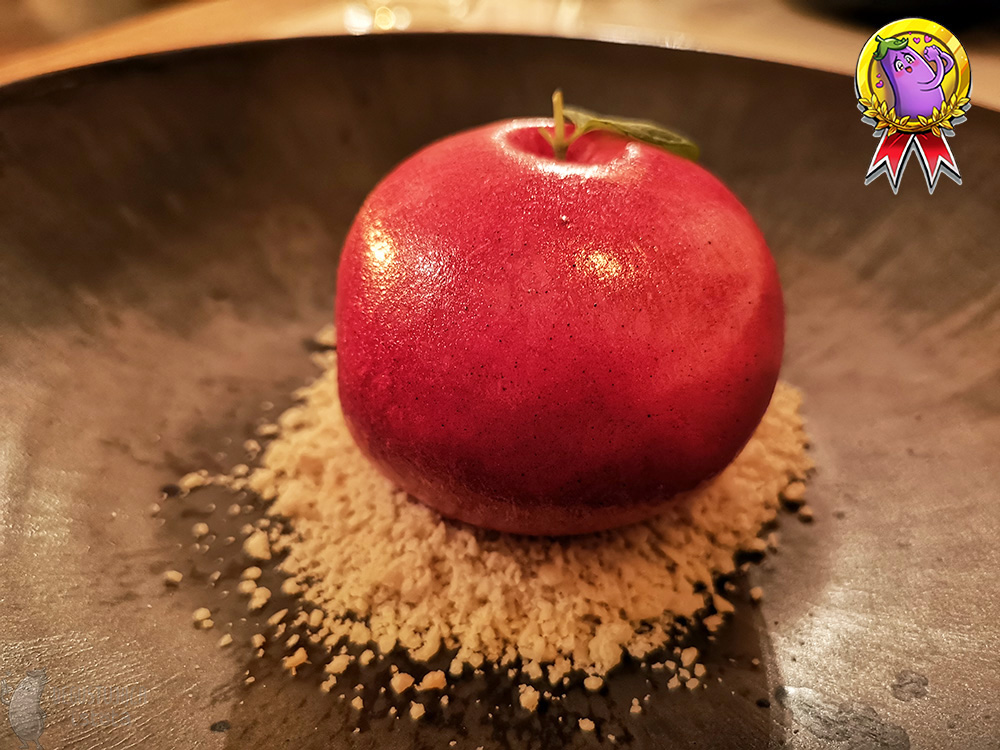 Imitation of red apple on a nut crumble, with a mint leaf at the top.