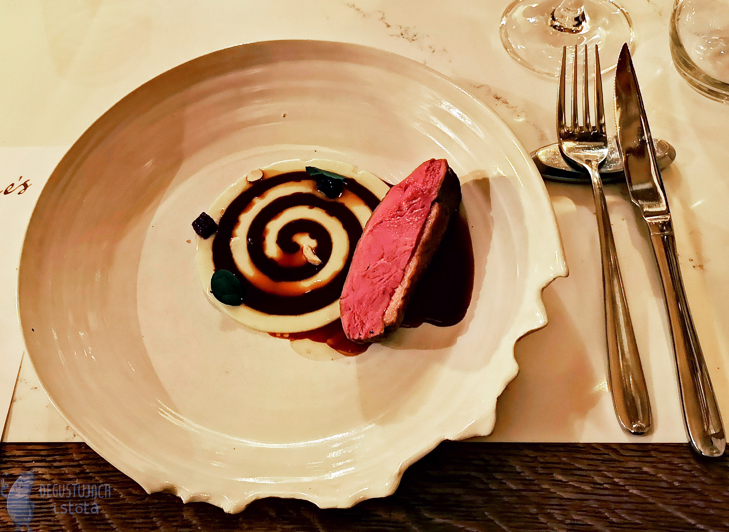 A snail stamp made of dark sauce on parsnip puree. Next to it is a duck fillet strap.