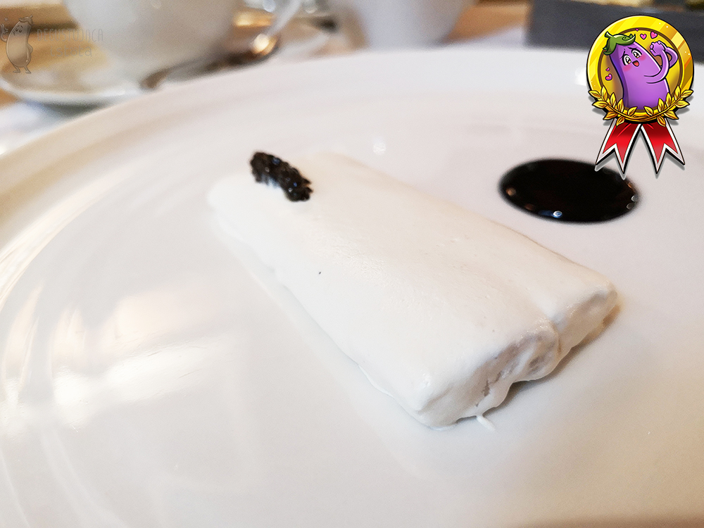 Eel fillet surrounded by horseradish foam with a bit of black caviar. Next to it is a circle of black elderberry sauce.