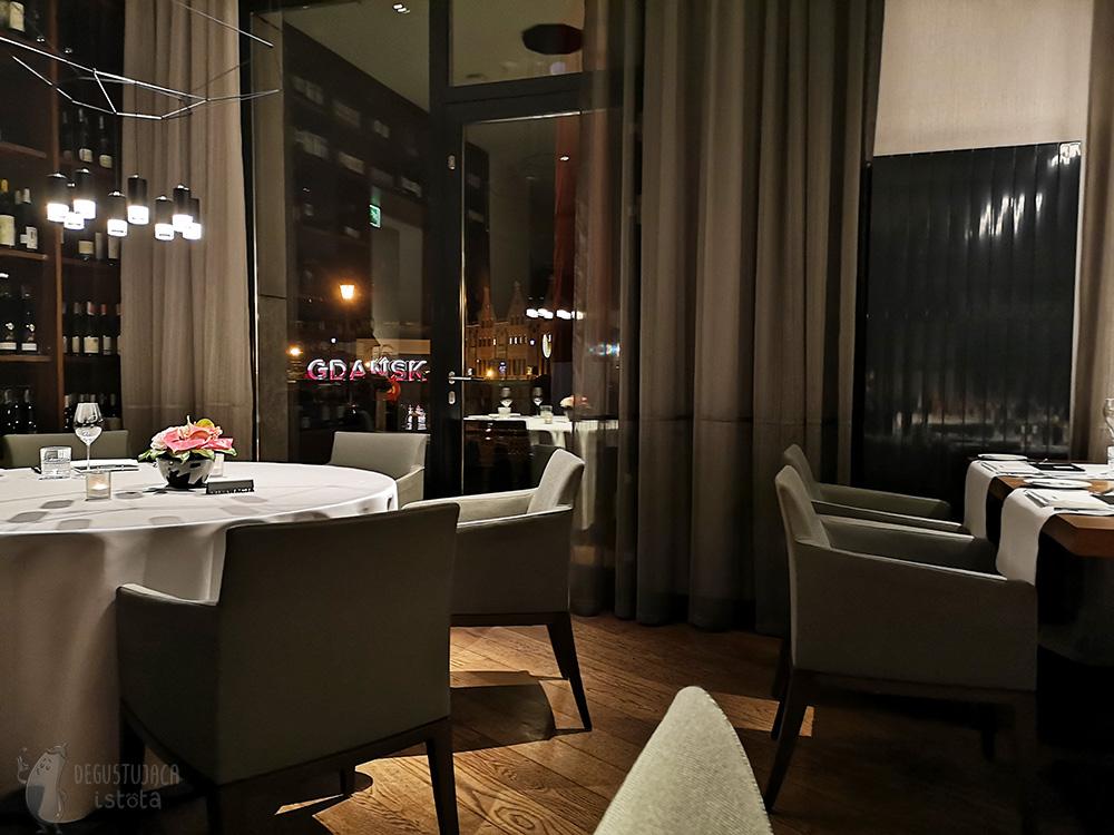 Stoliki z białymi obrusami i szare fotele w restauracji. Z okien widać biało czerwony napis Gdańsk, świecący w ciemności.