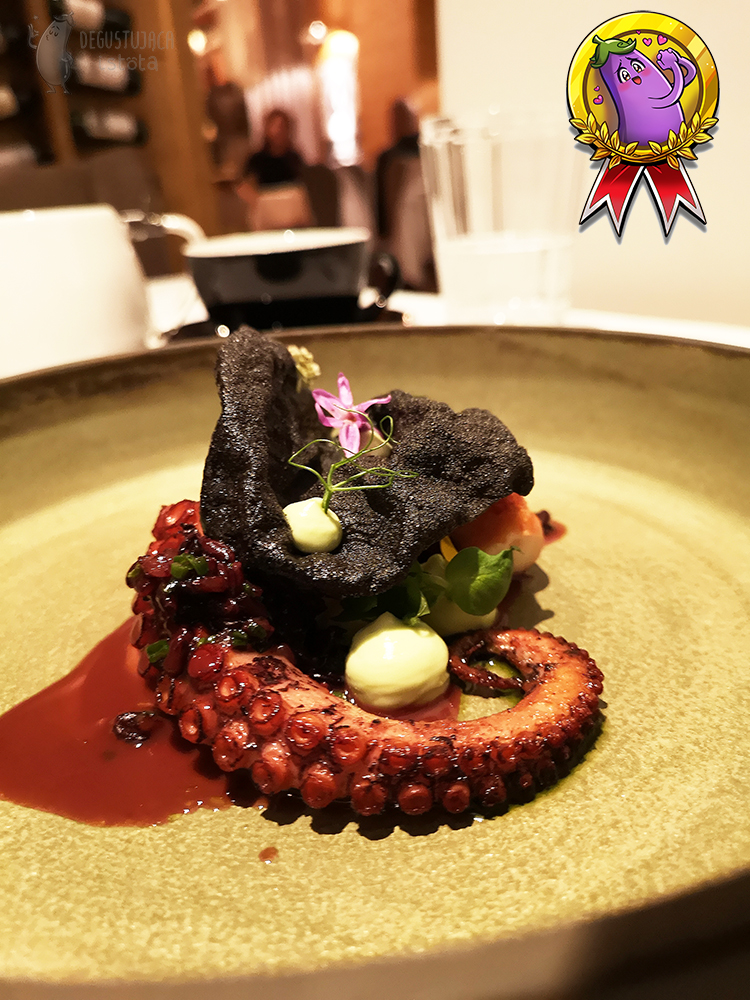 A piece of octopus tentacle with a black chip and slightly greenish mayonnaise applied. Decorated with a small pink flower.