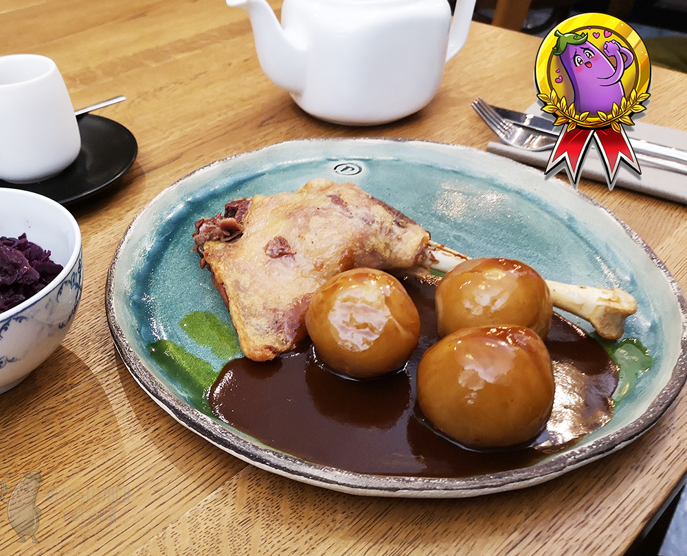 Goose leg on a light blue plate with round noodles. Next to it there is a visible piece of a bowl with red cabbage.