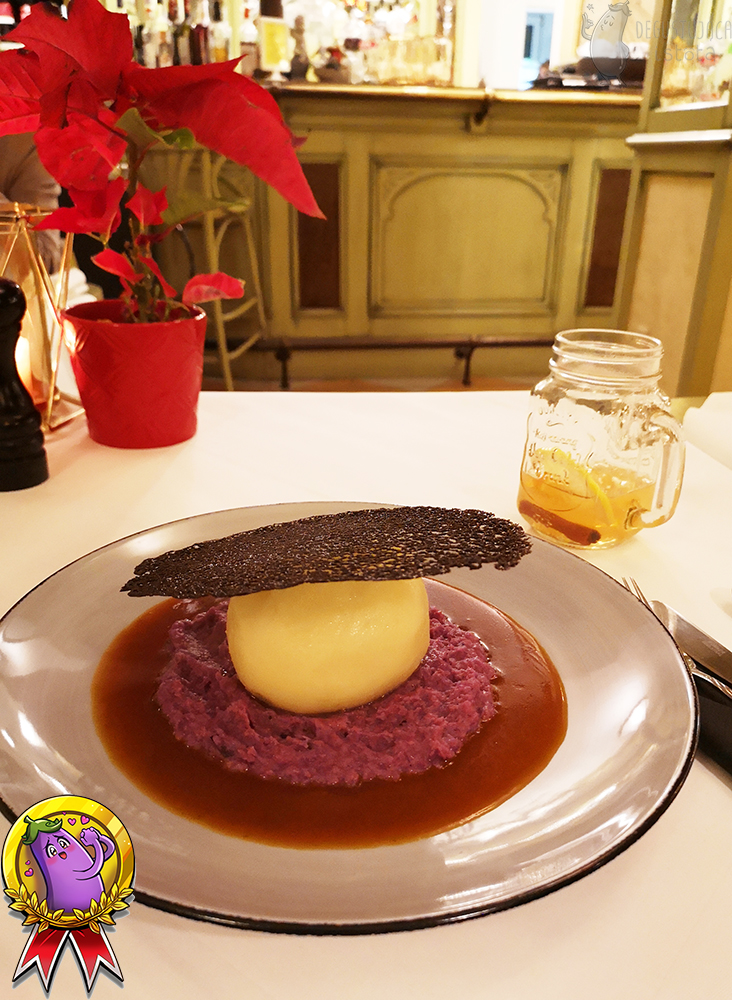 A large dumpling, placed on boiled, red cabbage, around which the sauce is poured. At the top of the noodle is a black lace made of dough with sepia.